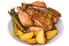 Getrenntes gebratenes vollständiges Huhn auf einer Platte Stockfoto