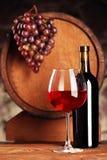 getrenntes OM waite Stillleben mit Glas und Flasche Rotwein Trauben und Fass defocused Selektiver Fokus Weinkelleratmosphäre stockfotos