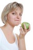 Getrenntes schönes blondes Mädchen mit einem Apfel Stockbilder
