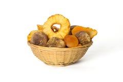 Getrocknete Ananas, Aprikosen und Feigen in einem Weidenkorb lokalisierten O Lizenzfreie Stockbilder