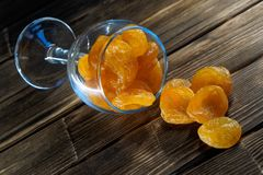 Getrocknete Aprikosen in einem Glasbecher auf einer Holzoberfläche stockbild