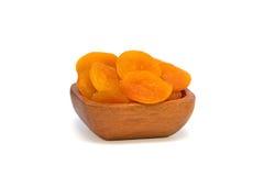Getrocknete Aprikosen in einer hölzernen Schüssel auf Weiß Stockbilder