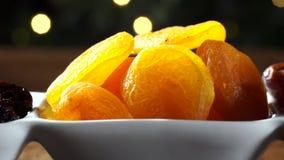 Getrocknete Aprikosen-, narbige und getrocknetebeere in einer Schüssel auf dem Brett mit unscharfem Weihnachtshintergrund stock footage