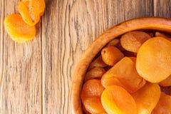 Getrocknete Aprikosen, Trockenfrüchte in einer hölzernen Platte Rustikale Art Er Lizenzfreie Stockbilder