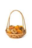 Getrocknete Aprikosen und Feigen in einem Weidenkorb lokalisiert auf Weiß Lizenzfreies Stockfoto