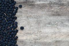 Getrocknete aronia Beeren auf hölzernem Hintergrund Stockfotografie