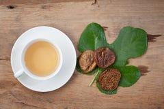 Getrocknete Feige und Tee auf Holztisch Stockbilder
