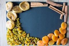 Getrocknete Feigen, Rosinen, Aprikosen und Zimt auf einem schwarzen Hintergrund Stockfoto