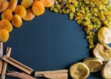 Getrocknete Feigen, Rosinen, Aprikosen und Zimt auf einem schwarzen Hintergrund Lizenzfreies Stockbild