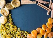 Getrocknete Feigen, Rosinen, Aprikosen und Zimt auf einem schwarzen Hintergrund Lizenzfreies Stockfoto