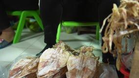 Getrocknete Fische Die geschnittenen Fischkonserven und säubern die Kalmarlage Auf einem Zähler in Marktvielen getrocknet stock footage