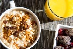 Getrocknete Frühstückseinstellung der Feigen, des Hafermehls und des Orangensaftes Stockfotografie