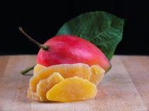 Getrocknete Mangoscheiben mit ganzer reifer Frucht auf hölzernem Hintergrund Lizenzfreie Stockbilder