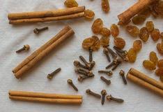 Getrocknete Nelken, Zimt und Rosinen auf einem hellen Gewebe Stockfoto