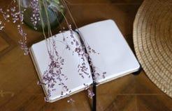 Getrocknete rosa Wildflowers und geöffnetes leeres Notizbuch Stockbild
