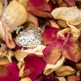 Getrocknete Rose Petals mit einem Herz-Anhänger stockfotos