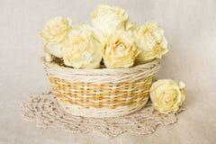 Getrocknete Rosen im Korb mit Doily Stockfoto