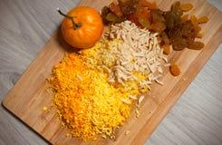 Getrocknete Rosine, gehackte Mandeln und zerquetschte Mandarinenoberteile auf hölzernem Brett über grauem hölzernem Hintergrund,  lizenzfreies stockfoto