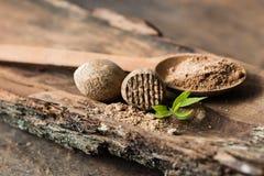 Getrocknete Samen der wohlriechenden Muskatnuss und zerriebenen der Muskatnuss lokalisiert auf weißem Hintergrund lizenzfreie stockbilder