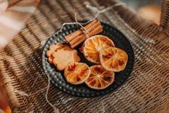 Getrocknete Scheiben von Orangen, von Lebkuchenplätzchen und von Zimtstangen auf Schwarzblech Stockbilder