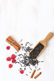 Getrocknete Teeblätter, Zimt und Himbeeren auf weißem Hintergrund Lizenzfreies Stockfoto