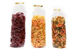 Getrocknete Teigwaren in der Vorderansicht der Tasche Bunte Gemüseteigwaren auf weißem Hintergrund stockfoto