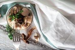Getrocknete und marinierte Pilze in der Kiste auf hölzernem Hintergrund Stockbild