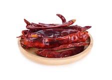 Getrockneter glühender Paprika ohne Stamm in der hölzernen Platte auf weißem backgr Lizenzfreies Stockfoto
