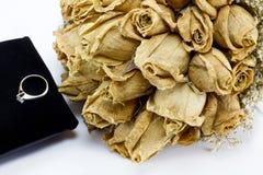 Getrockneter Roseblumenstrauß und Verlobungsring Stockbilder