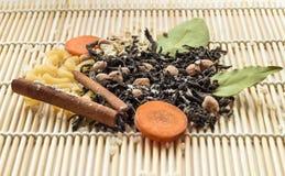 Getrockneter Tee, Teigwaren, Karotte und Gewürze auf hölzernem Hintergrund, Vorderansicht Stockbild