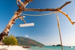 Getrockneter toter Baum mit Seil und ein leerer Signage vor einem beac Lizenzfreie Stockbilder