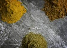 Getrocknetes gemischtes organisches Gewürz pulverisiert auf einem Marmorküche worktop Hintergrund, der von oben fotografiert wird lizenzfreies stockfoto
