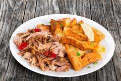 Getrokken langzaam-gekookt die varkensvlees in oven met gebraden aardappel wordt geroosterd stock afbeeldingen