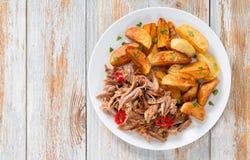 Getrokken langzaam-gekookt vlees dat in oven met gebraden aardappel wordt geroosterd royalty-vrije stock foto