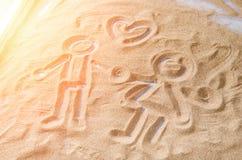 Getrokken op de zandcijfers van een man en een vrouw Royalty-vrije Stock Afbeelding