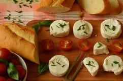 Gets ost med gräslökar, körsbärsröda tomater, basilika och bagetten på träskärbräda Royaltyfri Foto