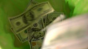 Gettando i soldi via, i dollari cadono nel canestro verde della pattumiera, libertà da finanza, sprecante i soldi archivi video