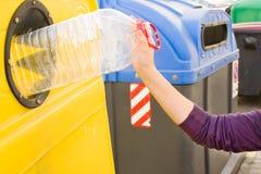 Gettando una bottiglia nel contenitore di riciclaggio Immagini Stock
