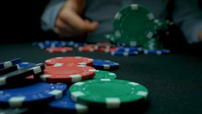 Getti i titoli di prim'ordine in mazza Blu e rosso che giocano i chip di poker nel fondo nero riflettente Primo piano dei chip di fotografia stock
