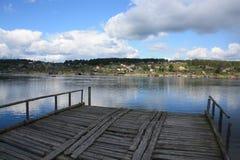 Getti un ponte sul villaggio di legno del mare delle nuvole del tramonto del pilastro della spiaggia Immagini Stock Libere da Diritti