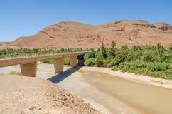 Getti un ponte sulla misurazione sopra il letto di fiume asciutto con alcune acqua, montagne e palme nel Marocco, Nord Africa Fotografia Stock Libera da Diritti