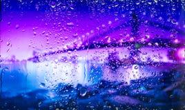 Getti un ponte sulla vista di A della città da una finestra da una parte migliore durante la pioggia Fuoco sulle gocce Immagine Stock