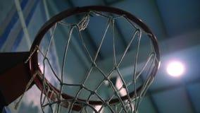 Getti una palla nell'anello di pallacanestro contro il contesto dei proiettori Movimento lento video d archivio