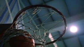 Getti una palla nell'anello di pallacanestro contro il contesto dei proiettori Movimento lento stock footage