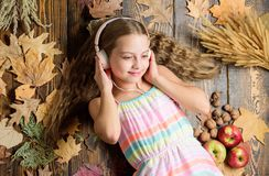 Getting into an autumnal mood. Adorable music fan on autumn background. Little girl listening to music in headset. Small royalty free stock image