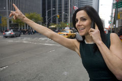 Getting Cab. Woman executive hails a cab while talking on a cell phone in a busy urban area royalty free stock images