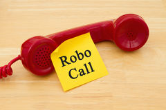 Getting a call from a Robocall. Retro red phone handset with a yellow sticky note and text Robocall Stock Images
