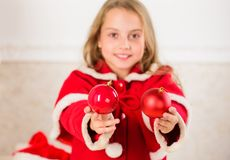 Getting child involved decorating. How to decorate christmas tree with kid. Girl smiling face hold balls ornaments white. Interior background. Let kid decorate royalty free stock photo