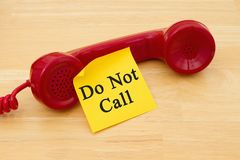Getting on the do not call list. Retro red phone handset with a yellow sticky note and text Do not call royalty free stock photo
