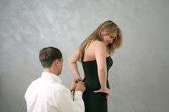 Getting dressed. Man helping woman get dressed Stock Photos